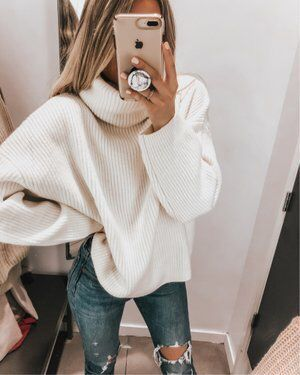 Cozy oversized white knit sweater with trendy ripped denim jeans .